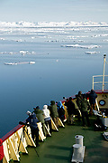"""Eco-tourists and photographers on the bow of the expedition vessle """"Polar Star"""" watching for exciting events in the ice off north-western Spitsbergen"""