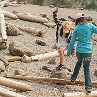 Children play on logs by Moraine Lake in Banff National Park, Alberta, Canada.