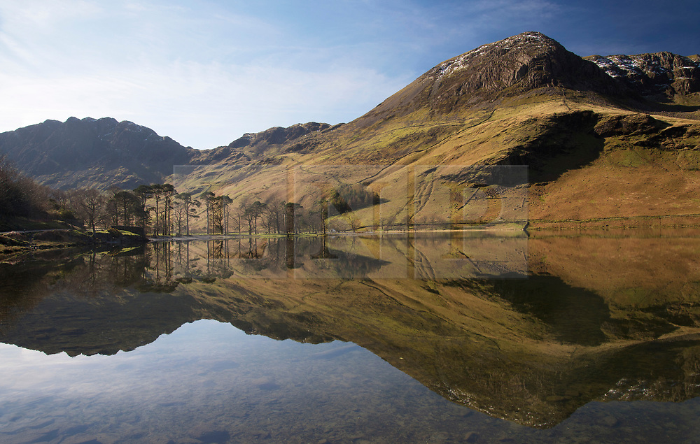 © Licensed to London News Pictures. 26/03/2017. Buttermere, UK.  The fells are reflected in the waters of Buttermere in the Lake District.  Photo credit: Anna Gowthorpe/LNP