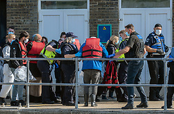 © Licensed to London News Pictures. 10/10/2021. Dover, UK. Border force officials escort migrants  into Dover Docks, Kent. 1,115 migrants are reported to have crossed  the Channel over a two day period. Photo credit: Stuart Brock/LNP