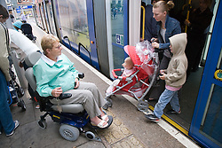 Family getting off the tram whilst wheelchair user waits to board,