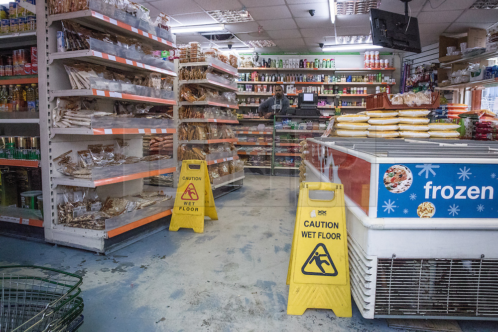 © Licensed to London News Pictures. 27/11/2016. London, UK. 'Caution Wet Floor' signs in a grocery store on Lee High Road which suffered flood damage after a tourist coach fell into a sinkhole. The road has been closed off and police declared a 'major incident' after a French tourist coach with 100 passengers on board fell into a sinkhole caused by a burst water mains, flooding a long stretch of the road including many local businesses. . Photo credit: Rob Pinney/LNP