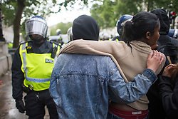 © Licensed to London News Pictures. 06/06/2020. London, UK. A white protester put her arm around a black protester, while stood next to a police officer in riot gear, in Westminster, central London during a Black Lives Matter demonstration over the killing of African American George Floyd. The death of George Floyd, who died after being restrained by a police officer In Minneapolis, Minnesota, caused widespread rioting and looting across the USA. Photo credit: Ben Cawthra/LNP