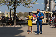 People eating ice cream in the sunshine on the South Bank next to Tower Bridge during hot and sunny weather on April 20, 2018 in London, England. Yesterday the United Kingdom experienced the hottest day in April since 1949, with temperatures reaching 27.9C 82.2F in London.