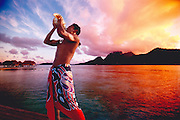 A man, native to Tahiti, blows into a conch shell on the beach.
