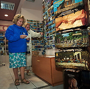 Two ladies are shopping in a tourist trinket store in the Plaka shopping centre, the largest official Olympic merchandising outlet in downtown Athens. The 29th modern Olympic circus is gearing up for business and official and unofficial souvenirs are on sale here, including postcards and table mats with various works of art available on a rack. We see the Parthenon on the Acropolis Hill, Michelangelo's 'Hands of God and Adam' image from the Sistine Chapel. 'Last Supper' by Leonardo da Vinci and a landscape from ancient Olympia, the birthplace of modern athletics and of the Olympic ideal. The Olympics came home to Greece in 2004 amid the woodland of ancient Olympia where for 1,100 continuous years, the ancients held their pagan festival of sport and debauchery. Corruption, politics, cheating and commercialism interfered with the ancient and modern games.