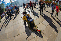 A one legged Tibetan pilgrim prostrating himself repeatedly as he circumambulates through Barkhor Square and along The Barkhor (around the area of the Jokhang Temple), the most sacred temple in Tibet, Lhasa, Tibet, China.
