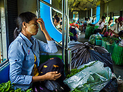 25 NOVEMBER 2017 - YANGON, MYANMAR: A passenger on the Yangon Circular Train. The Yangon Circular Train is a 45.9-kilometre (28.5 mi) 39-station two track loop system connects satellite towns and suburban areas to downtown. The train was built during the British colonial period, the second track was built in 1954. Trains currently run both directions (clockwise and counter-clockwise) around the city. The trains are the least expensive way to get across Yangon and they are very popular with Yangon's working class. About 100,000 people ride the train every day. A a ticket costs 200 Kyat (about .17¢ US) for the entire 28.5 mile loop.    PHOTO BY JACK KURTZ