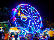 20 NOVEMBER 2015 - BANGKOK, THAILAND:  The Ferris Wheel at the Wat Saket temple fair. Wat Saket is on a man-made hill in the historic section of Bangkok. The temple has golden spire that is 260 feet high which was the highest point in Bangkok for more than 100 years. The temple construction began in the 1800s in the reign of King Rama III and was completed in the reign of King Rama IV. The annual temple fair is held on the 12th lunar month, for nine days around the November full moon. During the fair a red cloth (reminiscent of a monk's robe) is placed around the Golden Mount while the temple grounds hosts Thai traditional theatre, food stalls and traditional shows.    PHOTO BY JACK KURTZ