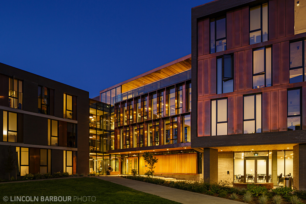 An evening photo of Trillium Residence Hall all lit up and glowing.