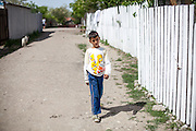 A boy walking one of the main streets in the Roma area of Frumusani.