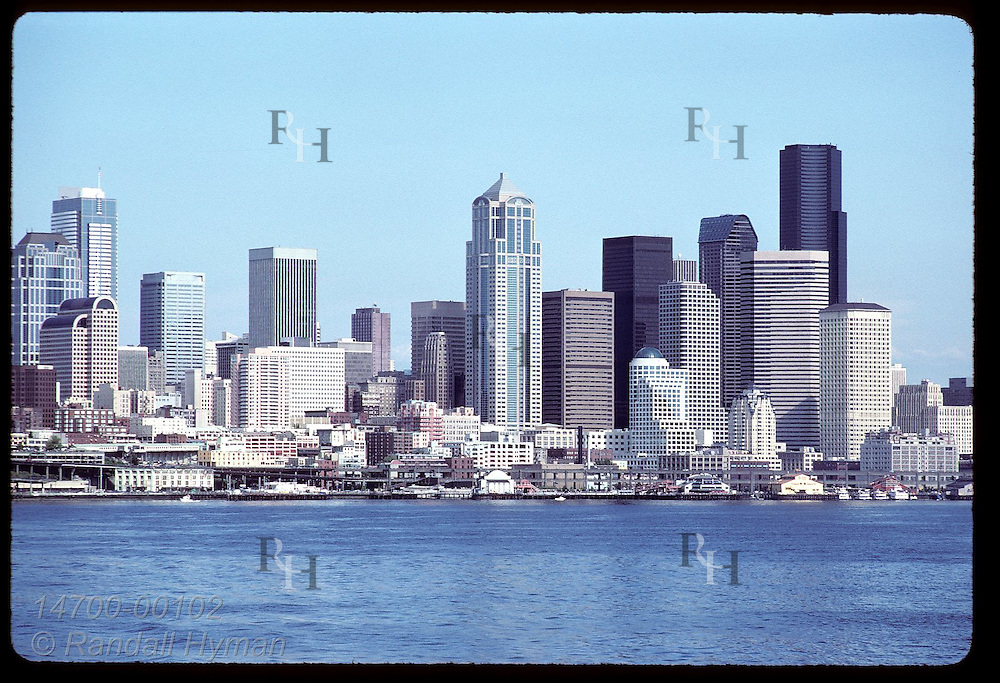 Modern skyscrapers loom over Puget Sound shore, dominating the skyline of downtown Seattle. Washington