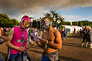 Two lost boys in mexican wrestlers outfits refer to a map at the Glastonbury Festival 2016. The Glastonbury Festival is the largest greenfield festival in the world, and is now attended by around 175,000 people. Its a five-day music festival that takes place near Pilton, Somerset. In addition to contemporary music, the festival hosts dance, comedy, theatre, circus, cabaret, and other arts. Held at Worthy Farm in Pilton, leading pop and rock artists have headlined, alongside thousands of others appearing on smaller stages and performance areas.