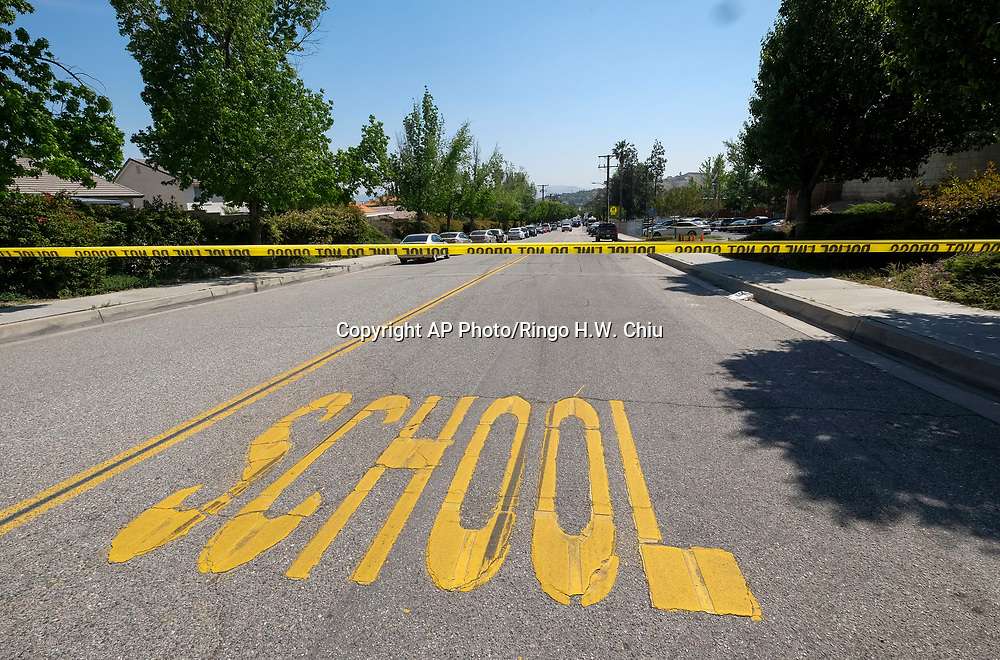 A police yellow tap is seen outside North Park School after a shooting ,Monday, April 10, 2017, in San Bernardino, Calif.. An apparent murder-suicide inside an elementary school classroom in San Bernardino left two adults dead, including a teacher, and two students wounded, police and school officials said. (AP Photo/Ringo H.W. Chiu)
