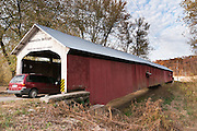 """Roseville Covered Bridge (263 feet long) was built in Burr Arch style over Big Raccoon Creek in 1910 by Van Fossen in Parke County, Indiana, USA. Red and white paint protects the wood. The """"Cross this bridge at a walk"""" sign requires slow vehicle speed."""