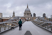 Woman walking her dog over a very quiet Millennium Bridge towards St Pauls Cathedral as the national coronavirus lockdown three continues on 28th January 2021 in London, United Kingdom. Following the surge in cases over the Winter including a new UK variant of Covid-19, this nationwide lockdown advises all citizens to follow the message to stay at home, protect the NHS and save lives.
