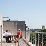 Three business colleagues enjoying the sun whilst having a breakout business meeting, set against the London skyline.