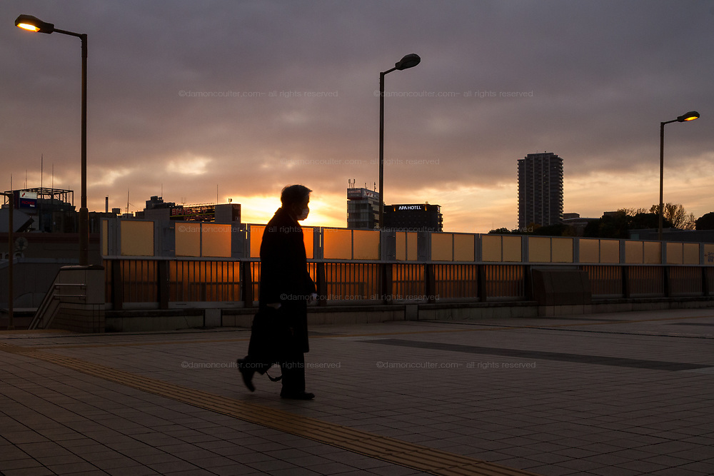 A salaryman, wearing a facemark, walks in front of the sunset from Panda Bridge in  Ueno, Tokyo, Japan Thursday December 10th 2020