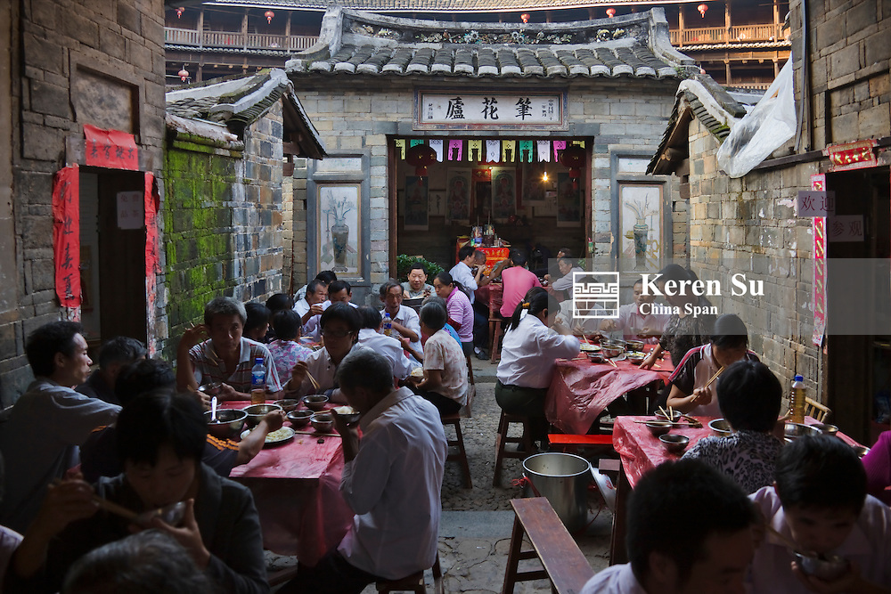 Family having a banquet inside Chengqi Tulou in Gaobei Tulou Cluster, UNESCO World Heritage site, Yongding, Fujian, China
