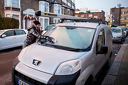 © Licensed to London News Pictures. 12/12/2017. London, UK. A commuter cleans frost from her car's windscreen in Wood Green, north London as temperatures drop below -3C across the capital overnight on Tuesday, 12 December 2017. Photo credit: Tolga Akmen/LNP
