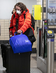 © Licensed to London News Pictures. 28/02/2020. London, UK. A Passengers at Victoria Tube Station, London wears a protective mask as fears of a pandemic increase after six cases of Coronavirus are confirmed in the UK in the last 24 hours. Photo credit: Alex Lentati/LNP