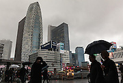 People with umbrellas brave rainy weather in front of the Cocoon Tower in Shinjuku, Tokyo, Japan. Friday January 29th 2016