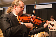 """Pieter Affourtit plays with one of his snakewood baroque-style bows with a """"pike"""" or """"swan-bill"""" head."""