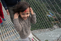 A young Nepali girl crossing the Kusma Gyadi Bridge, the tallest (443') and one of the longest (1,128') suspension bridges in the country that cut a hike of many hours to just a few minutes. Day-7 of our Himalayan Heroes adventure riding from Tatopani to Pokhara, Nepal. Monday, November 12, 2018. Photography ©2018 Michael Lichter.