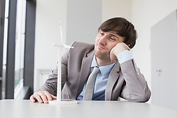 Businessman looking at wind power model