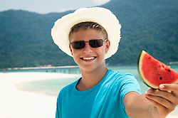 smiling teenage boy holding a piece of watermelon, Koh Lipe, Thailand