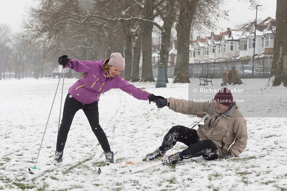 A cross-country skier helps pick up an elderly companion who has fallen over during their city ski through Ruskin Park in Lambeth, during a snowstorm in the city, on 28th February 2018, in London, England.