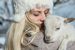 Teenage girl holding lamb, Bavaria, Germany