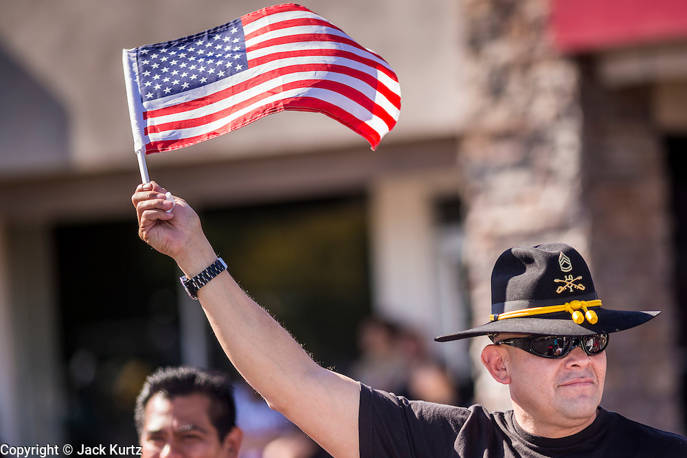 """11 NOVEMBER 2013 - PHOENIX, AZ: A veteran waves an American flag at the Phoenix Veterans Day Parade. The Phoenix Veterans Day Parade is one of the largest in the United States. Thousands of people line the 3.5 mile parade route and more than 85 units participate in the parade. The theme of this year's parade is """"saluting America's veterans.""""    PHOTO BY JACK KURTZ"""