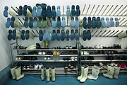 Many pairs of anti-slip Acifort Wellington boots are awaiting users at the New England seafood suppliers in Chessington, London England. Made by British company Dunlop, these boots are designed as protection against the cold , insulating wearers in refrigerated workplaces such as this facility where fresh fish is processed ready for supplying UK supermarkets. Either showing their soles or standing on the floor alongside the wearers' outdoor footwear, they are coloured various shades of clean off-white or soiled cream. New England Seafood is a major supplier of fresh and frozen premium sustainable fish and seafood in the UK and one of the largest importers of fresh tuna. The Wellington boot -or wellie - was worn and popularised by Arthur Wellesley, 1st Duke of Wellington and fashionable among the British aristocracy in the early 19th century.