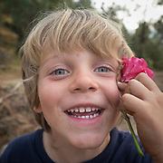Child is happy, holding a flower.