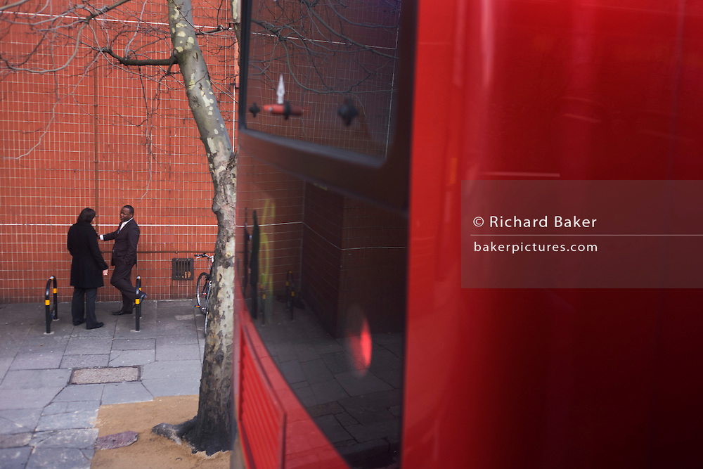 Two male smokers stand chatting outside their University building, seen from top deck of a London bus.