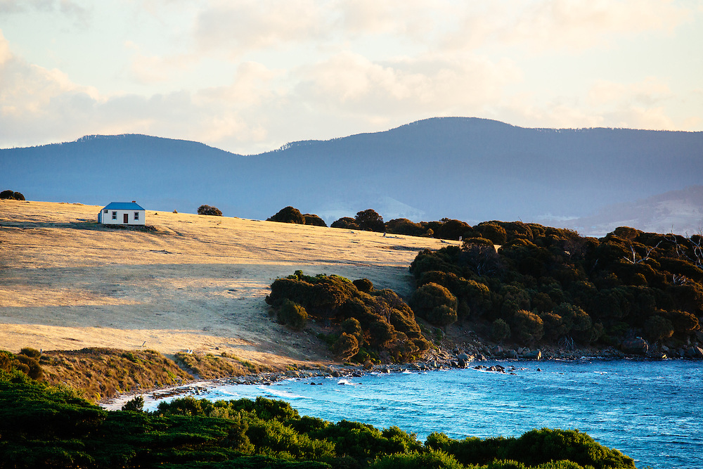 The idyllic seaside Ruby Hunts Cottage sitting up on a a cleared hill in Darlington. Maria Island National Park.