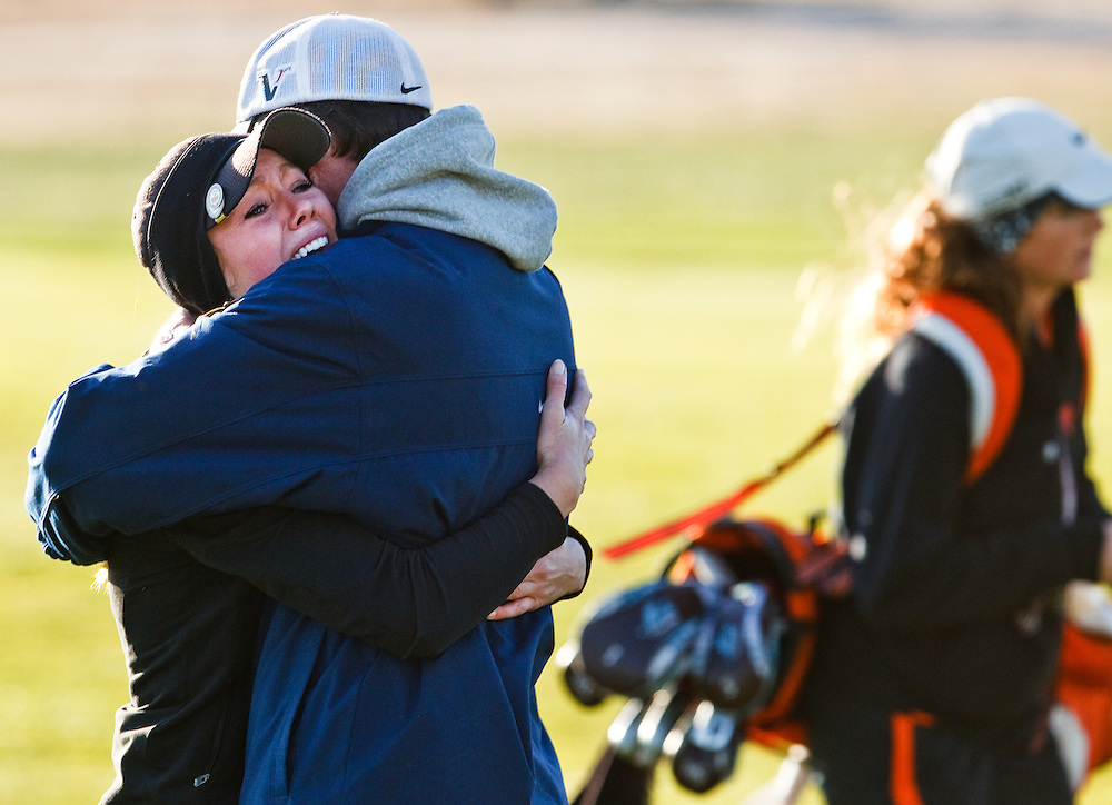 Grand Island Central Catholic senior McKenna Kime embraces her father, Dallas, after winning the Class C Individual Championship in the first round of a playoff against Ogalla's Maaika Mestl, back right, Tuesday at Quail Run Golf Course in Columbus. Her team also claimed the state title, beating Ogallala by five strokes. (Independent/Matt Dixon)