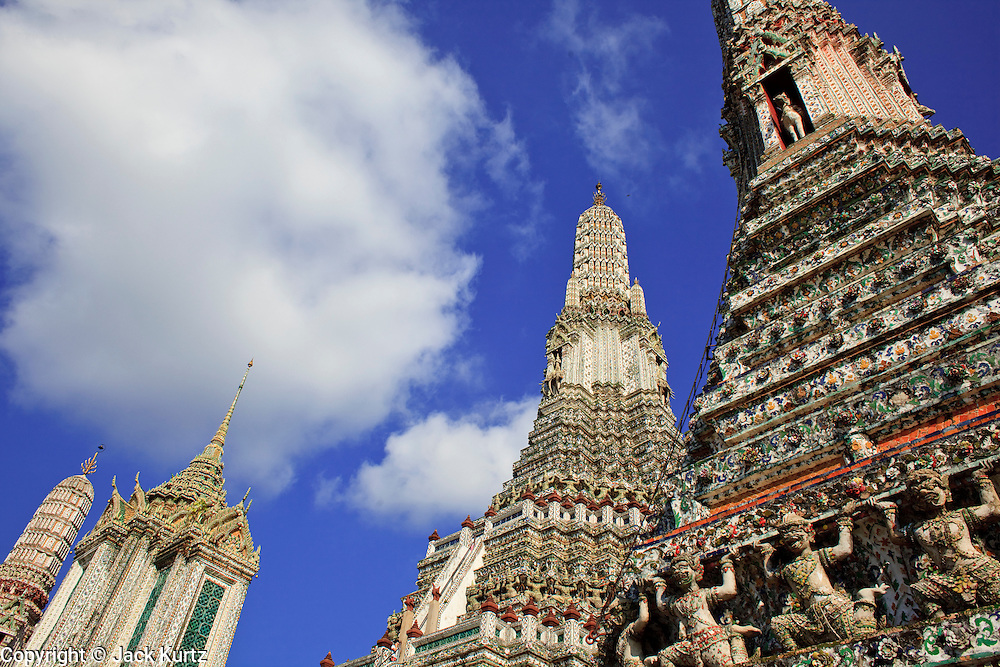 """09 MARCH 2009 -- BANGKOK, THAILAND: The central Prang at Wat Arun. Wat Arun is a Buddhist temple (wat) in the Bangkok Yai district of Bangkok, Thailand, on the west bank of the Chao Phraya River. The full name of the temple is Wat Arunratchawararam Ratchaworamahavihara. The outstanding feature of Wat Arun is its central prang (Khmer-style tower). It may be named """"Temple of the Dawn"""" because the first light of morning reflects off the surface of the temple with a pearly iridescence. Steep steps lead to the two terraces. The height is reported by different sources as between 66,80 m and 86 m. The corners are surrounded by 4 smaller satellite prangs. The prangs are decorated by seashells and bits of porcelain which had previously been used as ballast by boats coming to Bangkok from China. The central prang is topped with a seven-pronged trident, referred to by many sources as the """"trident of Shiva"""". Around the base of the prangs are various figures of ancient Chinese soldiers and animals. Over the second terrace are four statues of the Hindu god Indra riding on Erawan. The temple was built in the days of Thailand's ancient capital of Ayutthaya and originally known as Wat Makok (The Olive Temple). In the ensuing era when Thonburi was capital, King Taksin changed the name to Wat Chaeng. The later King Rama II. changed the name to Wat Arunratchatharam. He restored the temple and enlarged the central prang. The work was finished by King Rama III. King Rama IV gave the temple the present name Wat Arunratchawararam. As a sign of changing times, Wat Arun officially ordained its first westerner, an American, in 2005. The central prang symbolizes Mount Meru of the Indian cosmology. The satellite prangs are devoted to the wind god Phra Phai..Photo by Jack Kurtz"""