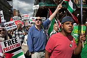London, UK. Saturday 9th August 2014. Protesters shout and gesticulate towards the American Embassy. Pro-Palestinian protesters in their tens of thousands march through central London to the American Embassy in protest against the military offensive in Gaza by Israel. British citizens and British Palestinians gathered in huge numbers carrying placards and banners calling to 'Free Palestine' and to 'End the seige on Gaza'.
