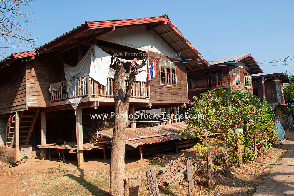 Traditional wooden Thai house elevated on stilts with corrugated iron roof