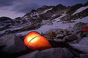 A tent glows at twilight in an alpine basin used as base camp for climbs of Glacier Peak in Glacier Peak Wilderness, Washington.