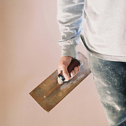 A plasterer from the maintenance department stands with a trowel in front of a newly plastered wall, Newby Hall estate and gardens, Ripon, North Yorkshire, UK