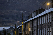 Slate mountains dominate local streets and terraced homes at dawn, on 3rd October 2021, in Blaenau Ffestiniog, Gwynedd, Wales. The derelict slate mines around Blaenau Ffestiniog in north Wales were awarded UNESCO World Heritage status in 2021. The industry's heyday was the 1890s when the Welsh slate industry employed approximately 17,000 workers, producing almost 500,000 tonnes of slate a year, around a third of all roofing slate used in the world in the late 19th century. Only 10% of slate was ever of good enough quality and the surrounding mountains now have slate waste and the ruined remains of machinery, workshops and shelters have changed the landscape for square miles.