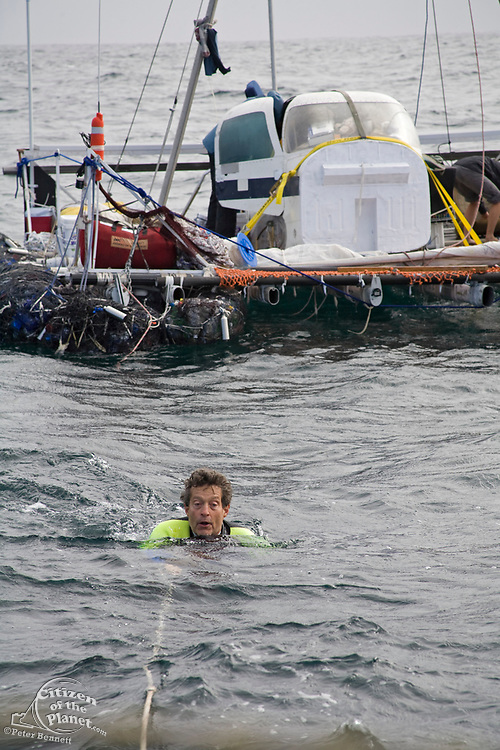 """Captain Charlie Moore swims over to the """"Junk"""" to bring some hot, fresh coffee. On Sunday June 1, the raft named """"Junk""""  left Long Beach for it's 2100 mile voyage to Hawaii to bring attention to the plastic marine debris (nicknamed the plastic soup) accumulating in the North Pacific Gyre. The raft was designed and will be sailed by Dr. Marcus Eriksen of the Algalita Marine Research Foundation, and Joel Paschal, it is constructed from 15,000 plastic bottles, an airplane fuselage, discarded fishing nets and a solar generator. The raft was towed for two and a half days to near San Nicholas Island, about 65 mile of the coast of California, so it could catch favorable winds for it's trip. The tow boat was the ORV Alguita, captained by Charlie Moore of the Algalita Marine Research Foundation, the man credited for first discovering the plastic soup in the Gyre over 12 years ago."""