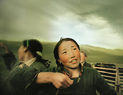 A young Mongolian girl gazes up at the sky after milking her yaks, in Western Mongolia.
