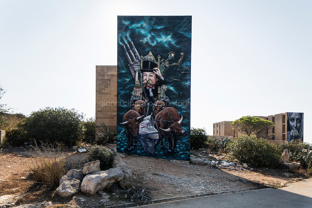 """PEMBROKE, MALTA - 28 AUGUST 2016: (L-R)  Graffitis by street artist """"Twitch"""" (James Grimaud), depicting the Monopoly man riding a cart driven by four oxen, and by street artist """"Clap"""", depicting a woman holding the world in her hands, are seen here on the the walls of an abandoned building of the White Rocks Complex in Pembroke, Malta, on August 28th 2016.<br /> <br /> The White Rocks area was originally developed as quarters for the British services. When the British left, the area was turned into a tourist complex but it eventually closed down and fell into ruins.<br /> <br /> While many cities across the world denounce the defacing of a public property, on the Mediterranean island of Malta it is encouraged.<br /> <br /> According to Sandra Borg of Arts Council Malta, street art projects """"engage with numerous communities and contribute directly to urban regeneration"""". Funding from Arts Council Malta, allows schools to offer additional creative arts subjects and many choose street art; with 'NO WAR' creator, James Grimaud, teaching students sketching, stencil making and aerosol use."""