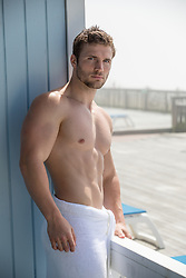 muscular man in a towel on a deck