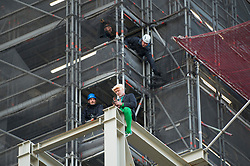 © Licensed to London News Pictures. 18/10/2019. LONDON, UK. A climate activist (green tights) from Extinction Rebellion on his mobile phone after scaling the construction scaffolding of the Queen Elizabeth Tower in Westminster. Parliament Square and the surrounding area has been brought to a standstill as police and emergency services assess the situation.  Photo credit: Stephen Chung/LNP