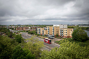 A red London bus drives down the A2041, passing the shopping area of Thamesmead, Greenwich, London. UK.